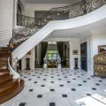 The Quebec mansion's foyer features a dramatic curved staircase and marble floor.